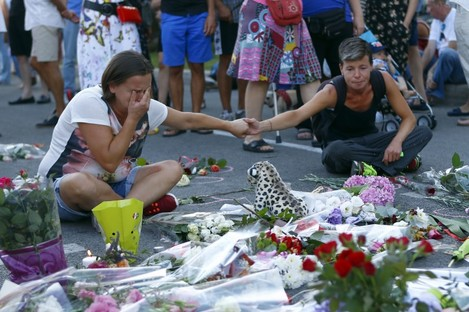 People pay tribute to the victims at the site of a deadly truck attack on the famed Promenade des Anglais in Nice, southern France in July.