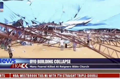 People stand at the scene after the roof of The Reigners Bible Church International collapsed onto worshippers