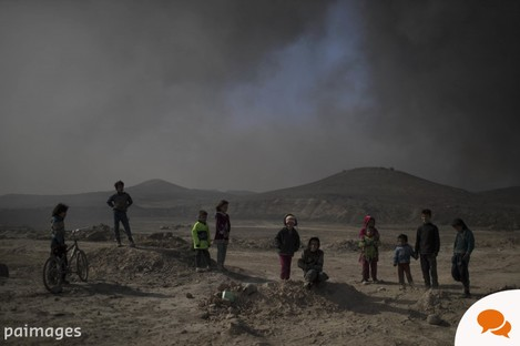 Children stand among smoke from burning oil fields in Qayara, south of Mosul.