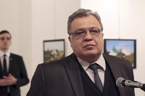 Andrei Karlov, the Russian Ambassador to Turkey, speaks at a photo exhibition in Ankara with the gunman behind him.