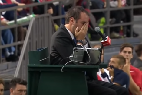 Umpire Arnaud Gabas holds his face.
