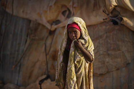 A young Somali girl stands outside her makeshift hut at a camp of people displaced from their homes elsewhere in the country by the drought, shortly after dawn in Qardho, Somalia.