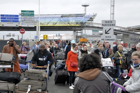 Passengers evacuated from Orly airport walk on the highway at Orly Airport yesterday.