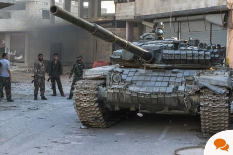 Syrian soldiers of the national army are near the tank after a battle with rebels in the suburbs of Damascus.
