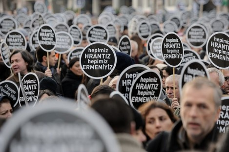 """Protesters hold signs reading """"We are all Hrant, we are all Armenian"""" as tens of thousands of protesters march to mark the fifth anniversary of Turkish-Armenian journalist Hrant Dink's murder in Istanbul, Turkey, Thursday, Jan. 19, 2012."""