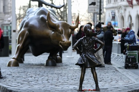 The Fearless Girl statue facing down the iconic bronze bull on Wall Street.