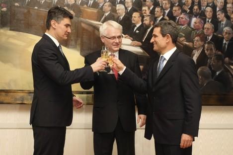 Croatia's president Ivo Josipovic, center, prime minister Zoran Milanovic, left, and the Parliament speaker Boris Sprem make a toast upon hearing unofficial results of the referendum last night