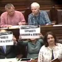Solidarity-PBP TDs refuse to stand for Dáil prayer and hold up 'separate Church and State' posters