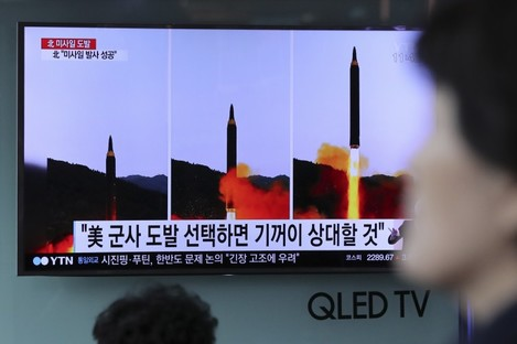 A woman walks by a TV news program showing images of North Korean missile launch, published in the country's Rodong Sinmun newspaper, at Seoul Railway station in Seoul.