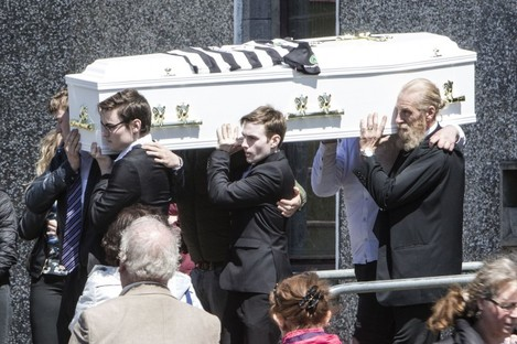 Conor's coffin carried by his friends and his father Greg (right).