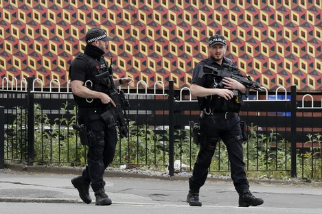 Armed police keep guard near Victoria Station in Manchester.
