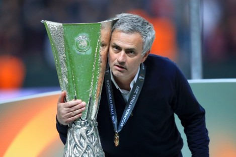 Manchester United manager Jose Mourinho celebrates with the trophy.