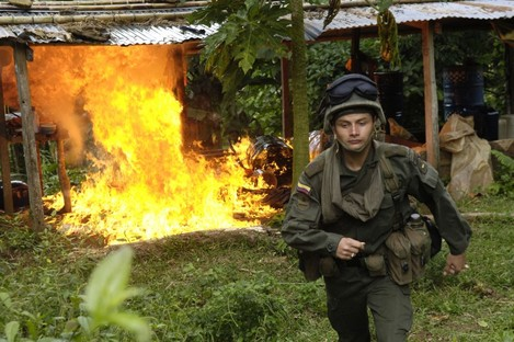 A Colombian anti-narcotic police officer  destroys a cocaine laboratory in Tolima, Colombia.
