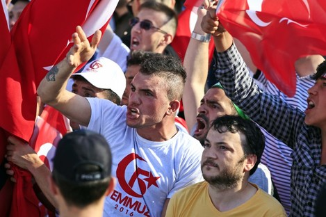 """People take part in the """"National Unity March"""" to commemorate the one year anniversary of the failed July coup."""