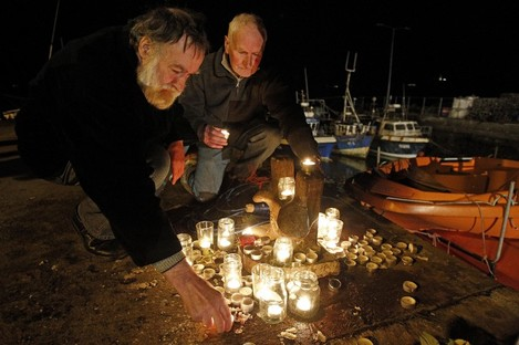 Candles are lit at a memorial on the pier at Union Hall.
