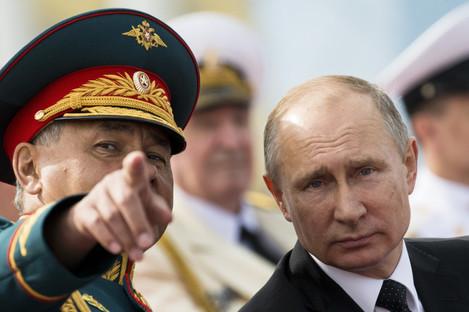 Russian President Vladimir Putin, right, listens to Defence Minister Sergei Shoigu .