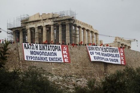 Greek communist parties hold banners at Athen's Acropolis hill.