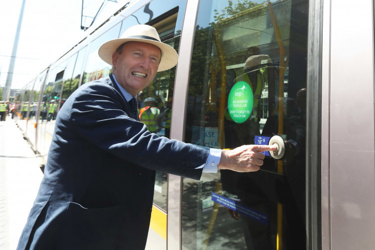 Pictured is Minister for Transport Shane Ross wearing a Bloomsday hat and about to step onto a Luas.