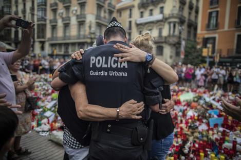 A policeman hugs to a boy and his family that he helped during the terrorist attack.