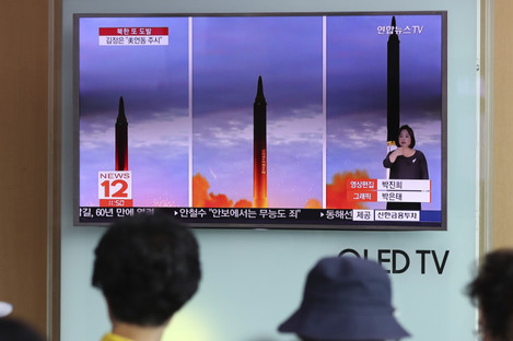People watch a news report about North Korea's missile launch at Seoul Train Station in Seoul, South Korea.