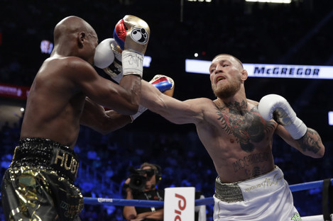 Conor McGregor hits Floyd Mayweather Jr in a super welterweight boxing match.