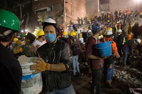 Volunteers and rescue workers remove rubble and search for survivors feared trapped in a collapsed building yesterday.