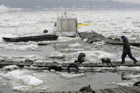 A man walks by damaged boats on a frozen part of the Danube River in Belgrade.