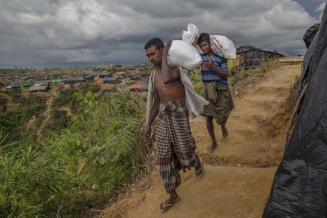 Rohingya Muslims who crossed over from Myanmar into Bangladesh, walk back to their shelters after collecting aid in Taiy Khali refugee camp, Bangladesh,.