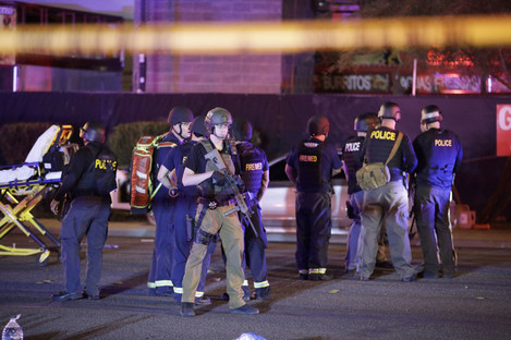 Police officers stand at the scene of the shooting