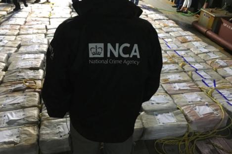 An NCA officer surveying the cocaine haul