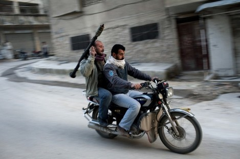 Supporters of the Free Syrian Army ride a motorcycle with a rocket-propelled grenade in Syria at the weekend