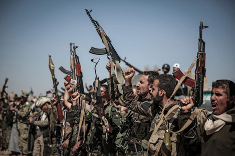 Houthi rebel fighters raise their weapons and chant slogans during a gathering aimed at mobilising more fighters before heading to battlefronts in Sanaa, Yemen.