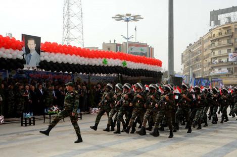 Syrian troops march past a portrait of Bashar al-Assad.
