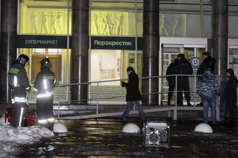 Police stand at the entrance of a supermarket, after an explosion in St Petersburg