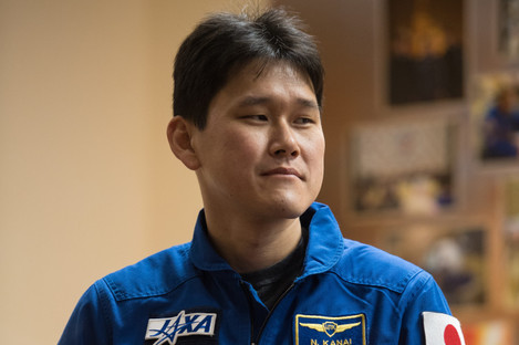 Expedition 54 flight engineer Norishige Kanai is seen in quarantine behind glass during a press conference in December 2017.