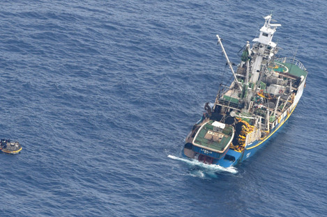 A fishing boat rescuing a dingy carrying six dehydrated adults and an unconscious baby.