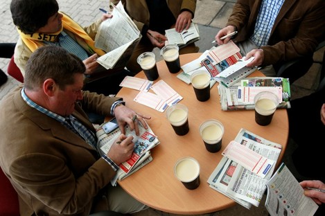 Race goers check form over a pint of Guinness  yesterday.