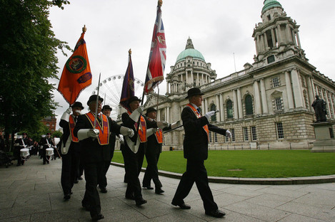 The Orange Order march past City Hall in Belfast.