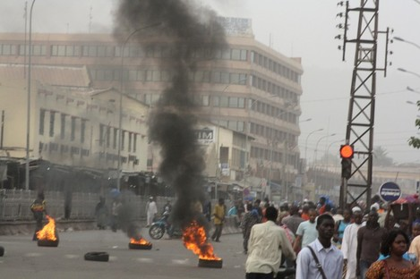 Civilians walk past burning tires lit in support of mutinying soldiers, in Bamako, Mali