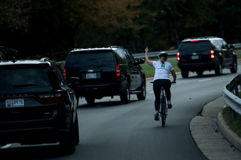 Juli Briskman gestures with her middle finger as a motorcade with US President Donald Trump departs Trump National Golf Course last October.