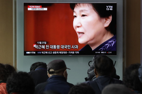 People watch a TV screen showing file footages of former South Korean President Park Geun-hye during a news program at the Seoul Railway Station in Seoul, South Korea.