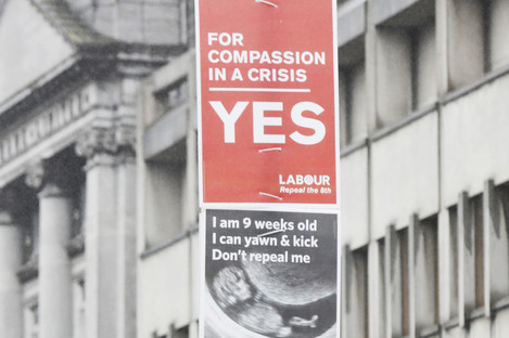 Posters from both sides on a pole at Dublin's College Green.