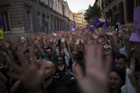 People lift up their arms as they shout slogans during a protest outside the Justice Ministry in Madrid.