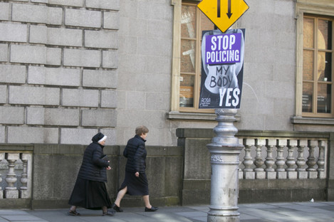 A nun walks past a Yes poster in Dublin earlier this month.