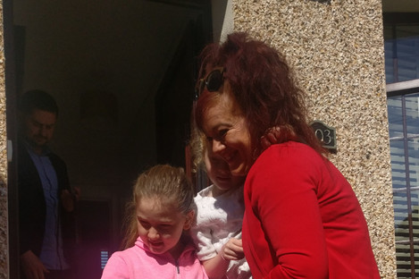 Toni and her two daughters in front of her new home.
