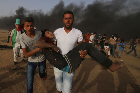 Palestinian protesters carry a wounded person during clashes with Israeli troops near the Gaza-Israel border on Friday.