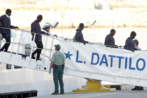 Migrants descend the Italian coast guard vessel Dattilo.