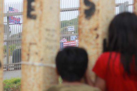Two Mexican children look at supporters of President Trump waving US-American flags and holding up signs in support of the wall in Tijuana, Mexico