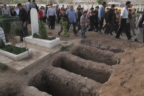 Mourners walk past open graves at a cemetery during the funeral for four people killed in a raid by government forces in a neighboUrhood of Damascus