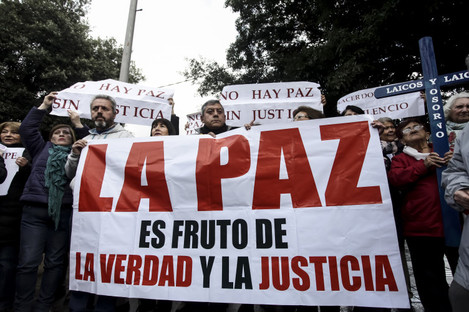 """File photos of lay members of the Catholic Church carrying a sign that reads in Spanish """"Truth and justice bear peace""""."""
